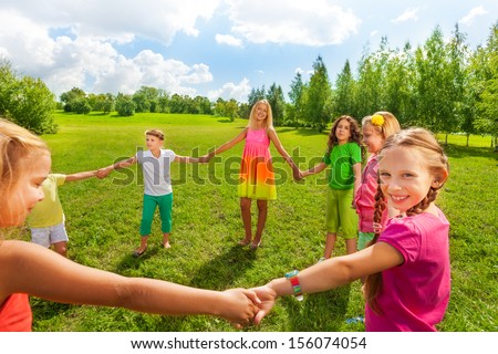Large group of happy smiling and dancing girls play roundelay and stand in circle in the park on the green grass on sunny summer day - stock photo