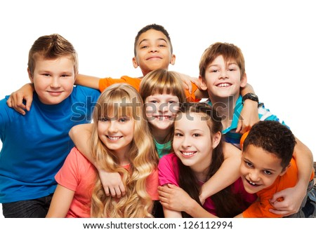 Large group of kids age 8-11 hugging, smiling and laughing, boys and girls - stock photo