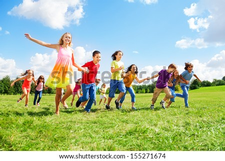 Large group of kids, boys and girls smiling and running in the park on sunny summer day in casual clothes
