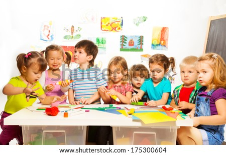 Large group of little kids painting with pencils and gluing with glue stick on art class in kindergarten - stock photo
