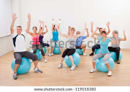 Large group of people doing pilates in a gym sitting on their balls with their arms raised practicing balance