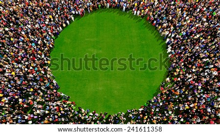 Large group of people seen from above, gathered in the shape of a circle, standing on a green grass background - stock photo