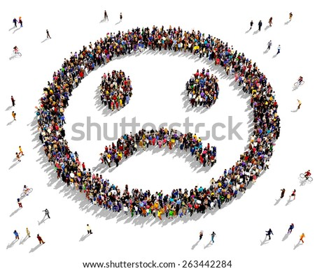 Large group of people seen from above gathered together in the shape of a sad face - stock photo