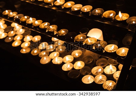 Large group of small candles burning on shelves in dark catholic church