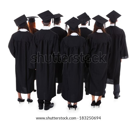 Large group of students graduating standing in the gowns and mortarboard hats viewed from behind isolated on white - stock photo