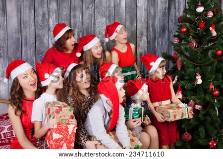 Large Group of surprised people in santa cluas hats holding presents and looking at Christmas tree - stock photo