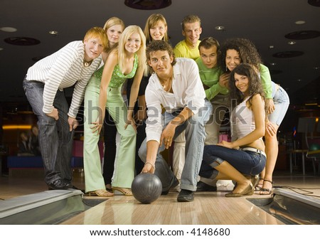 Large group of teenagers standing and smiling in bowling alley. One person is holding ball and playing. Looking at camera