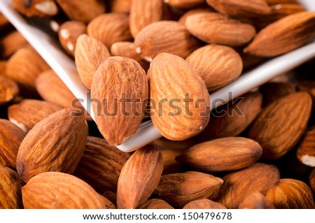 Large group of the raw almonds in white cup - stock photo