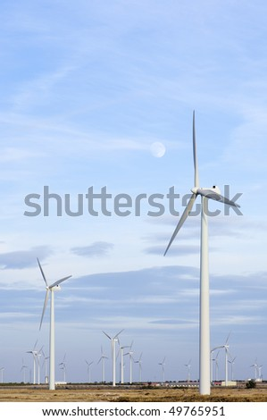 large group of windmills and moonlit sky at sunset - stock photo