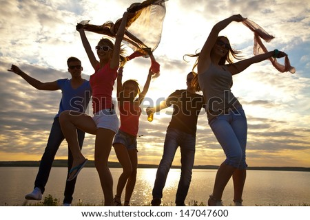 Large group of young people enjoying a beach party - stock photo