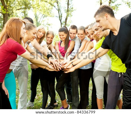 large group of young people with their hands together outdoor - stock photo