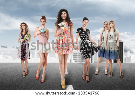 Large group of young women walking on road against abstract city - stock photo