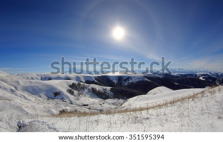 Large halo around the sun on a winter day in mountains Elbrus. North Caucasus, Russia. - stock photo