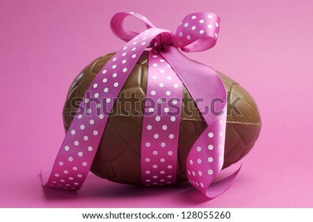Large Happy Easter chocolate Easter egg with pink polka dot ribbon tied in a bow against a pretty feminine pink background. - stock photo