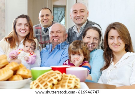 large happy three generations family drinks tea with baked at home