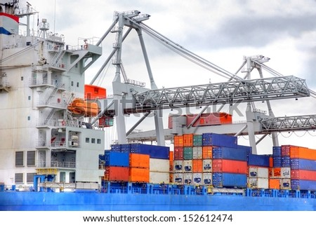 Large harbor cranes at the port of Rotterdam moving big metal containers from ships , Holland europoort big metal containers  - stock photo