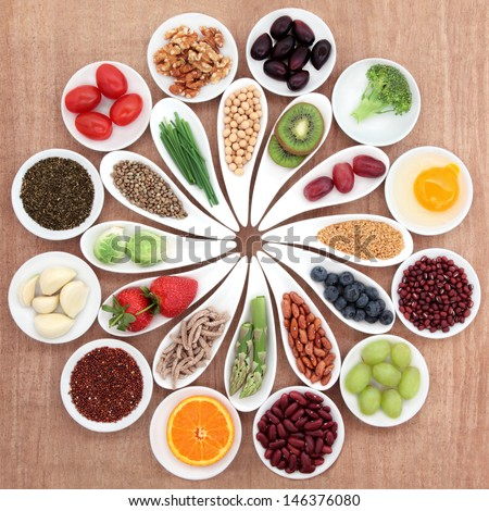 Large health food selection in white porcelain bowls and dishes over papyrus background. - stock photo