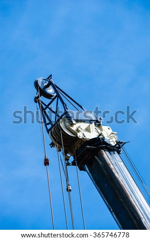 Large heavy industrial pulleys and cables on top of blue and white crane on partly cloudy blue sky, vertical shot.