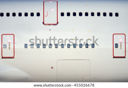 large heavy modern passenger widebody airplane side close up detailed exterior view with exit door handle
