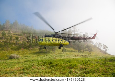 Large helicopter lands in the forest in the fog. - stock photo