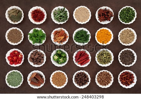 Large herb and spice collection in porcelain crinkle bowls over lokta paper background. - stock photo