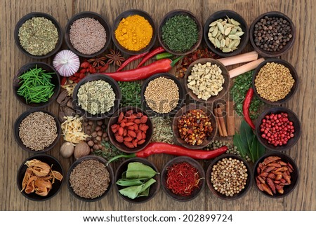 Large herb and spice sampler in wooden bowls and loose over oak wood background. - stock photo