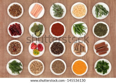 Large herb and spice sampler over papyrus background.