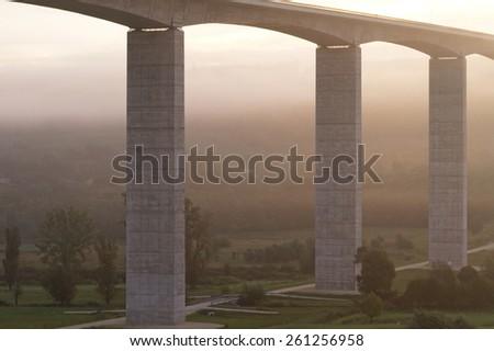 Large highway viaduct with foggy sunrise on autumn - stock photo