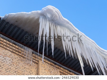 Large icicles hanging on the roof of the house in springtime - stock photo
