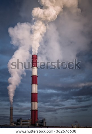 Large industrial chimney stack emits toxic pollutants into the sky creating global warming and polluting the natural environment