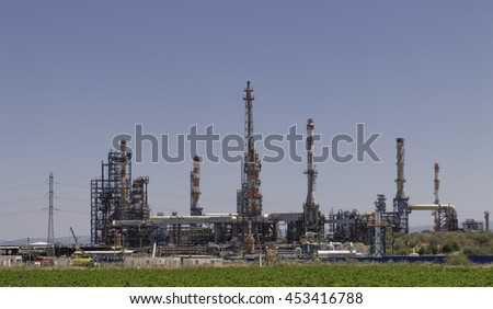 large industrial chimneys at refineries against green fields in haifa israel