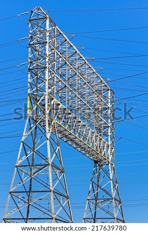 Large industrial electricity transmission tower or electricity pylon steel lattice grid structure. Array of wires, conductors and insulators. Blue sky background.  - stock photo