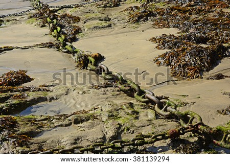 Large iron chain for mooring boats to, on beach at Newquay Harbour, Cornwall, England - stock photo