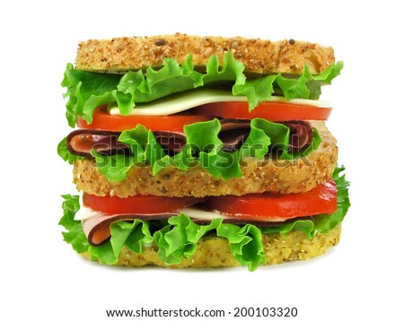 Large isolated sandwich on a whole grain bread with ham, tomato, lettuce and cheese