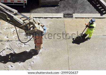 large jackhammer construction vehicle machine destroying pavement of a city street