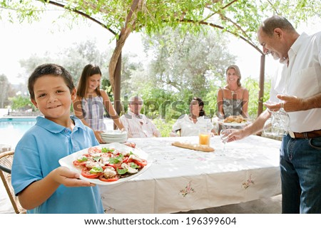 Large joyful family preparing a table outdoors together, placing plates, glasses and healthy food during a sunny holiday day in a vacation villa home garden, outdoors. Teamwork and eating lifestyle. - stock photo
