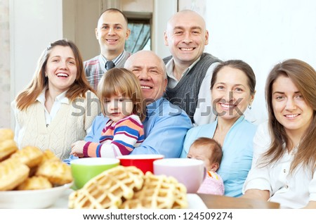 large joyful three generations family sits  in home - stock photo