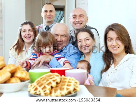 large joyful three generations family sits on sofa at home together - stock photo
