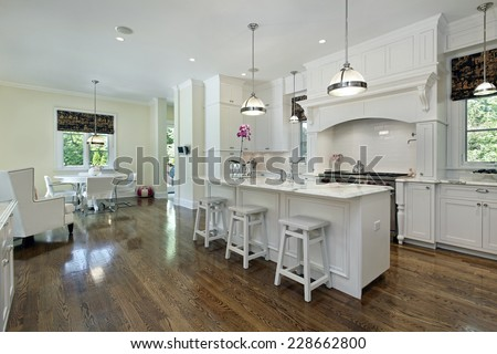 Large kitchen in luxury home with white cabinetry - stock photo