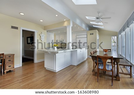 Large kitchen with table and white cabinetry