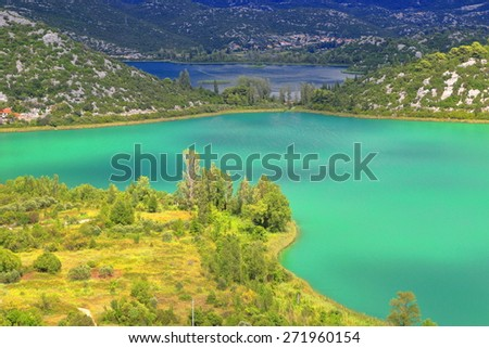 Large lake with green water within limestone hills near Neretva delta, Croatia - stock photo