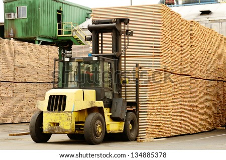 Large lift truck moving a stack of green fir 2 x 4 lumber studs at a small log processing mill in southern Oregon, ready for the drying kiln - stock photo