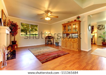 Large Living room with hardwood floor, red rug  and beige walls. - stock photo