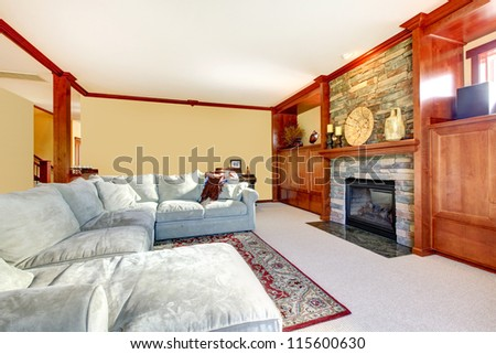 Large living room with sectional grey sofa and fireplace inside of wood build in cases. - stock photo