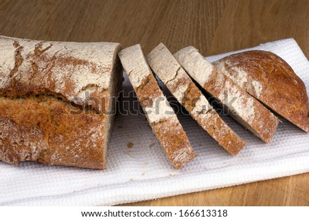 Large loaf of black bread with a crisp cut into slices on a white napkin