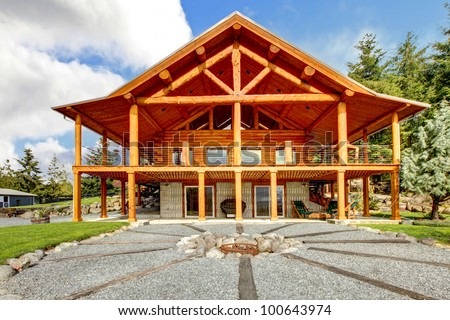 Large log cabin with large porch and fire circle - stock photo