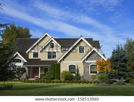 Large luxurious house with blue sky and landscaping - stock photo