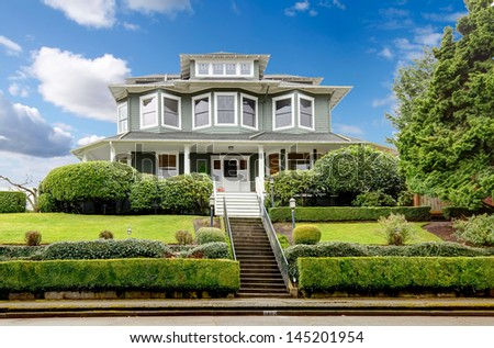 Large luxury green craftsman classic American house exterior. - stock photo