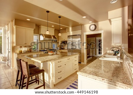 Large luxury kitchen room in beige colors with granite counter tops, stainless steel fridge and tile floor.