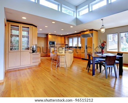 Large luxury modern wood kitchen with granite counter tops and yellow hardwood floor. - stock photo